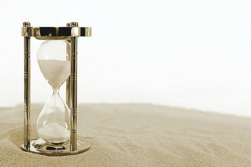 Golden sand timer standing on sand