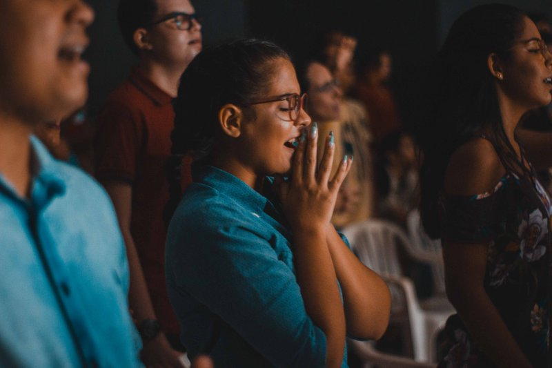People with eyes closed in audience. Photographer: Luan Cabral   Source: unsplash