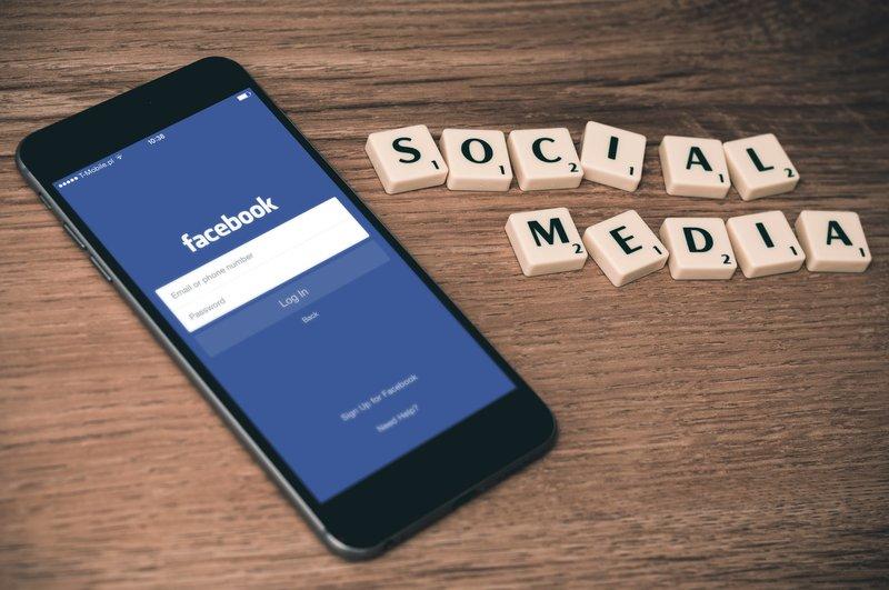 Smart phone on table with beside it scrabble tiles spelling social media