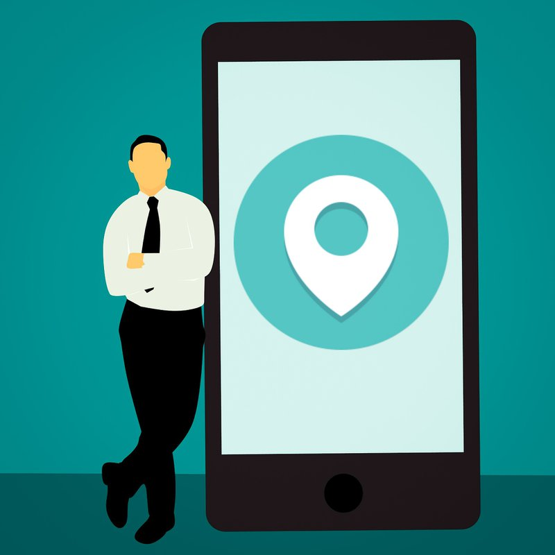cartoon of guy standing beside larger than life smartphone showing location icon