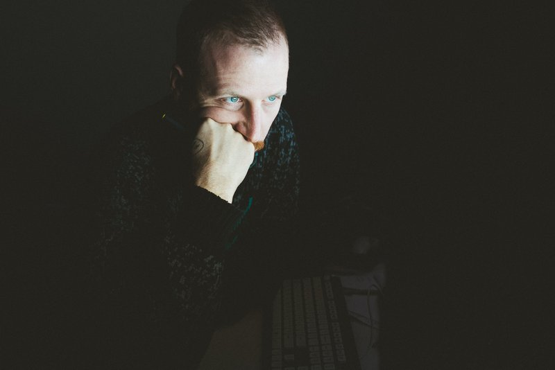guy in the dark with his face lit up by computer screen
