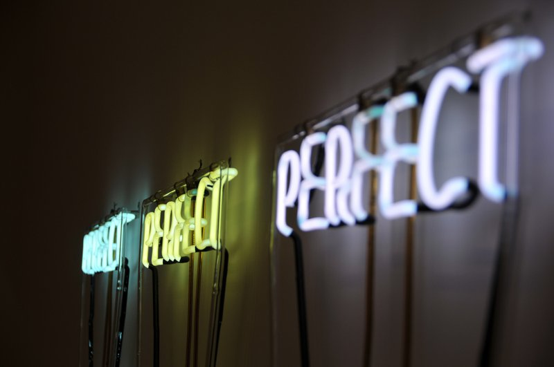 letter lights spelling PERFECT three times in a row on a wall // Photographer: Jonathan Hoxmark | Source: Unsplash