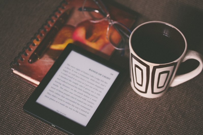 close up of kindle, coffee mug, notebook and glasses