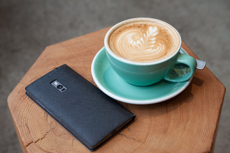 Phone in case and latte on a small coffee table / Photographer: Kim S. Ly | Source: Unsplash
