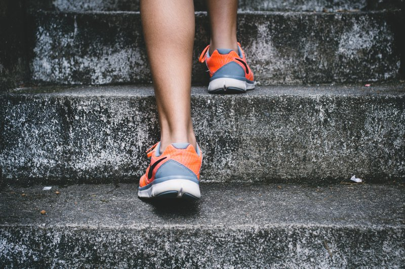 Close up of feet in sneakers walking up stone steps / Photographer: Bruno Nascimento | Source: Unsplash