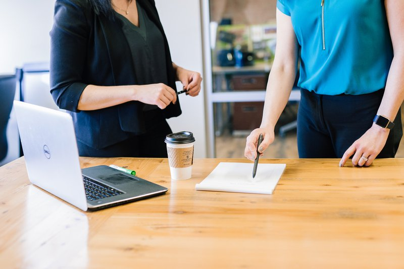 Two people standing at a desk with laptop, coffee, pen and paper on desk / Photographer: Amy Hirschi | Source: Unsplash