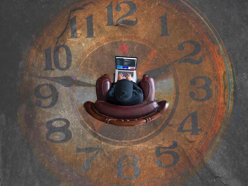 View from above of guy sitting on chair in the middle of  painted clock / Photographer: Kevin Ku | Source: Unsplash